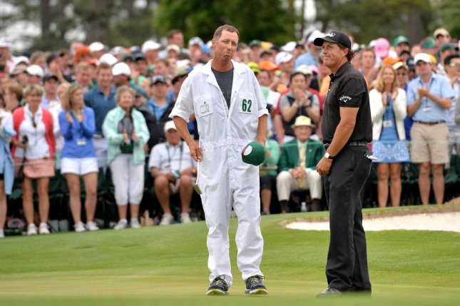 Phil Mickelson and caddie Jim Bones Mackay stand on the 18th green in the final round at the 2015 Masters Tournament at Augusta National Golf Club in Augusta, Georgia on April 12, 2015. Jordan Spieth won the 2015 Masters Tournament and it is his first major championship win with a score of 18 under par. Photo by Kevin Dietsch/UPI