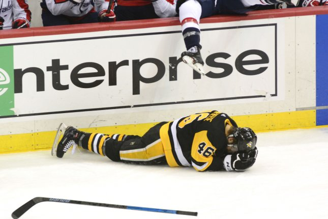 Pittsburgh Penguins center Zach Aston-Reese (46) lays face down on the ice after colliding with Washington Capitals right wing Tom Wilson (43) during the second period in Game 3 during the second round of the Eastern Conference 2018 NHL Stanley Cup Playoffs Tuesday at PPG Paints Arena in Pittsburgh, Pa. Photo by Archie Carpenter/UPI