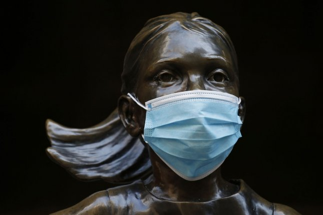 A mask covers the face of The Fearless Girl statue outside of The New York Stock Exchange. The markets rose Friday as drugmaker Gilead Sciences reported a positive study showing its antiviral remdesivir helped treat coronavirus. File Photo by John Angelillo/UPI