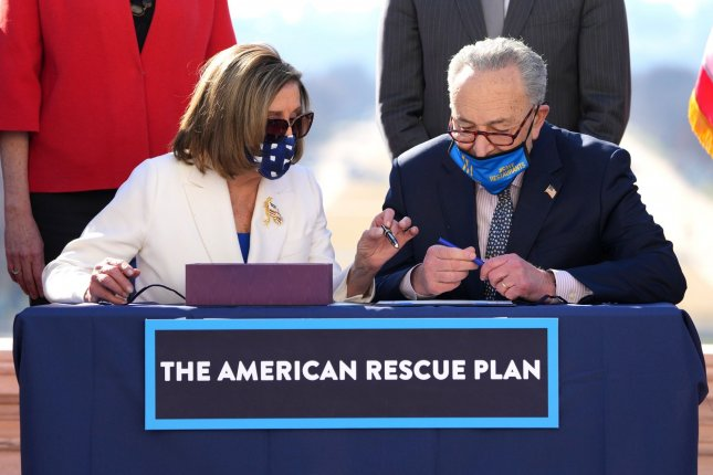 Speaker of the House Nancy Pelosi and Senate Majority Leader Charles Schumer sign the American Rescue Plan COVID relief bill on March 10. The stimulus bill produced a $660 billion budget deficit in March, officials said. File photo by Kevin Dietsch/UPI
