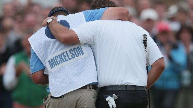 USA's Phil Mickelson embraces his caddie after winning the Open Championship at Muirfield. Mickelson won with a score of three under par. UPI/Hugo Philpott