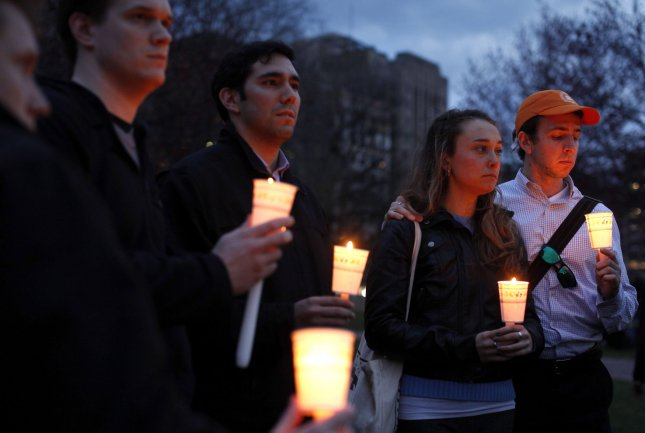 A group of people console one another at a candle at a candlelight vigil held at Boston Common in Boston, Massachusetts on April 16, 2013. The vigil is in response to the bombings on Boylston Street near the finish line of the Boston Marathon Monday afternoon killing 3 and injuring 150. UPI/Matthew Healey