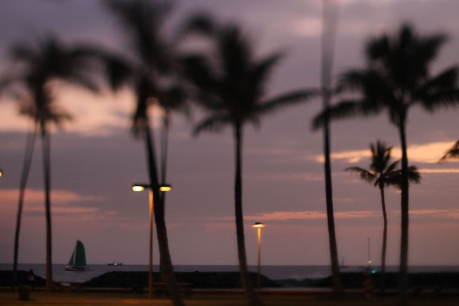 A lone sailboat sails offshore Magic Island next to Ala Moana Beach Park fronting the orange glow during sunset in Honolulu, Hawaii. File Photo by Cory Lum/UPI