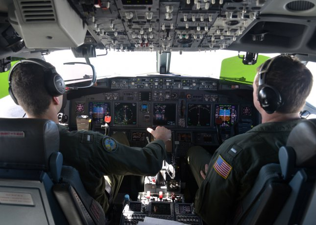 U.S. Naval aviator Lt. Kyle Atakturk (L) and Lt. Nicholas Horton pilot a P-8A Poseidon during a mission to assist in search and rescue operations for Malaysia Airlines flight MH370 in the Indian Ocean on March 19, 2014. The U.S. Navy Poseidon aircraft are assisting in the search for debris that was spotted by an Australian satellite that has been called a credible lead. The debris is some 1,500 miles off the western coast of Australia. UPI/Eric A. Pastor/U.S. Navy