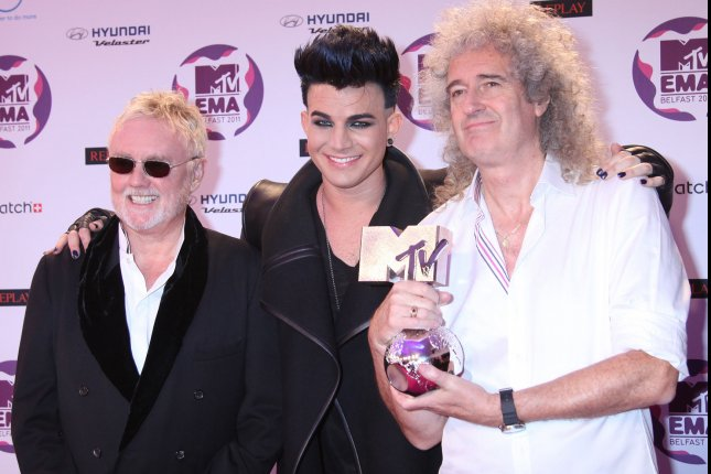 Roger Taylor (L) and Brian May (R) of Queen arrive on the red carpet with Adam Lambert after receiving the Global Icon Award at the MTV Europe Music Awards in Belfast, North Ireland on November 6, 2011. UPI/David Silpa
