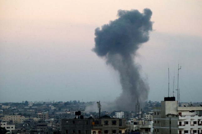Smoke billows from buildings following an Israeli air strike in Rafah, in the southern Gaza Strip, on July 31, 2014. Israel said they would stay in Gaza until the Palestinian tunnels were destroyed. . UPI/Ismael Mohamad