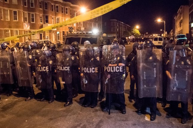 Police in riot gear line up with military rescue vehicle while local citizens pushed the limit of the 10 p.m. curfew in Baltimore, Maryland on April 28, 2015. Protests have erupted after death of Freddie Gray. Photo by Ken Cedeno/UPI