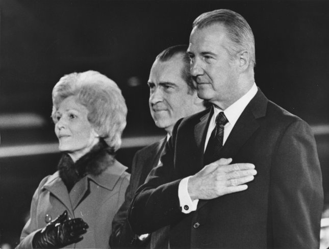 President Nixon, flanked by his wife and VP Spiro Agnew, stand at attention during the National Anthem upon the President's return from China on February 28, 1972. Several thousand well-wishers greeted Nixon at Andrew Air Force base. UPI File Photo