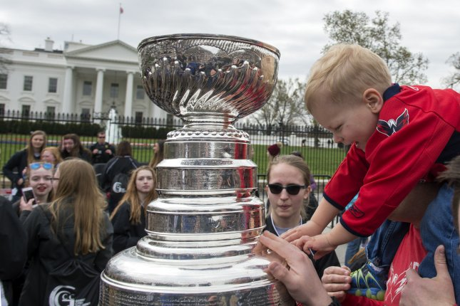 Dan Corrigan son James, 3, reaches to take a close look at the National Hockey League's (NHL) Stanley Cup that made a random stop in front of the White House in Washington, DC on March 30, 2017. The NHL is making random stops with the championship trophy in playoff cities with the playoffs starting soon. Corrigan is from Washington, DC. Photo by Pat Benic/UPI