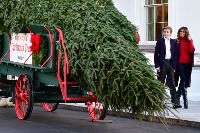 First lady Melania Trump, joined by son Barron Trump, receives the official White House Christmas tree from the Chapman family of Wisconsin at the White House in Washington, D.C., on Monday. Photo by Kevin Dietsch/UPI