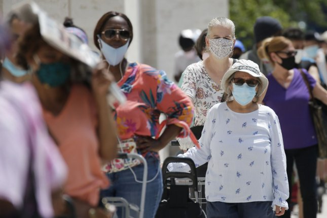People wear face masks as they wait in line to receive a bag of groceries at a food pantry at the Lincoln Center for the Performing Arts in New York City Wednesday. New York Gov. Andrew Cuomo said Saturday that he's waiting to see what happens with infection rates before deciding whether to open schools in the fall. Photo by John Angelillo/UPI