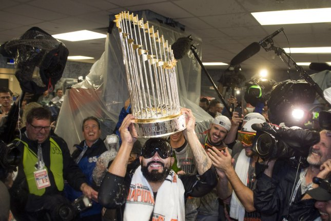 Sergio Romo of the San Francisco Giants celebrates with the Commissioner Trophy after the Giants won the 2014 World Series, defeating the Kansas City Royals at Kaufman Stadium in Kansas City, Missouri on October 28, 2014. UPI/Kevin Dietsch