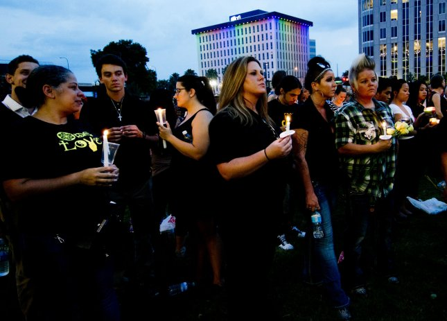 People jam the lawn of the Dr. Phillips Center for the performing arts on Tuesday for a candlelight vigil after the shooting at the Pulse nightclub. Such mass shootings appear to have become a part of our American cultural vernacular, a shared way for certain men to protest threats to their entitlement and defend the hierarchy their identities depend on. Photo by Gary I Rothstein/UPI