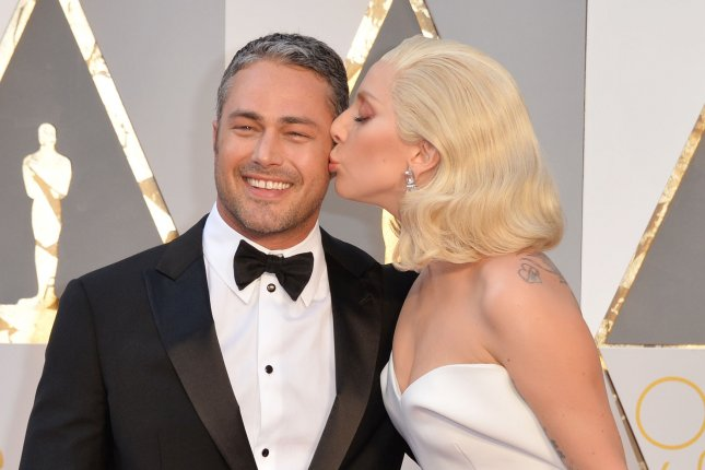 Lady Gaga (R) and Taylor Kinney at the Academy Awards on February 28. The couple started dating in 2011. File Photo by Kevin Dietsch/UPI