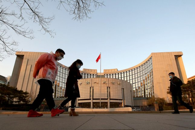People walk past the People's Bank of China, the country's central bank, in Beijing on Monday. Photo by Stephen Shaver/UPI