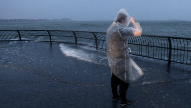 A woman watches the water spill over into Manhattan in Battery Park as Hurricane Sandy lands in souther New Jersey in New York City on October 29, 2012. UPI/John Angelillo