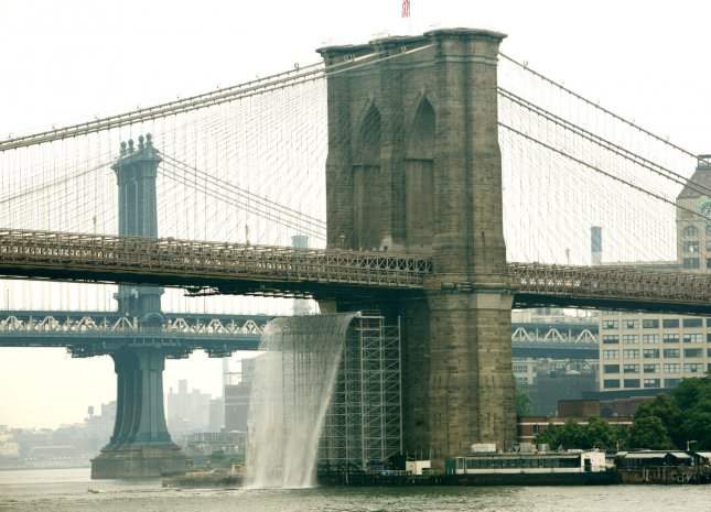An 80-foot waterfall pours out from under the Brooklyn Bridge, center, as part of the New York City Waterfalls installation, a series of man-made waterfalls situated along the East River on June 26, 2008 in New York. The four gigantic waterfalls made of steel frames is the work of Danish artist Olafur Eliasson and will be displayed until October 13. (UPI Photo/Monika Graff)