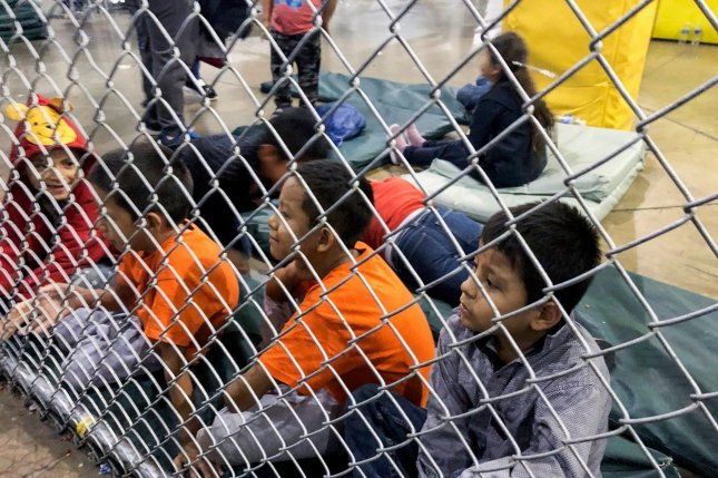Detained children sit on pads behind cyclone fencing at the Central Processing Center in McAllen, Texas, in July. File Photo courtesy of U.S. Rep. Doris Matsui's office