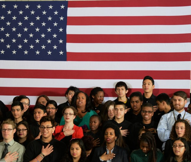 Teachers and students recite the Pledge of Allegiance prior to the arrival of President Barack Obama at Buck Lodge Middle School in Adelphi, Md., on February 4, 2014. On June 14, 1954, the phrase under God was formally added to U.S. Pledge of Allegiance. File Photo by Pat Benic/UPI