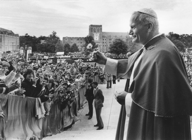 Holding a flower in his hand, Pope John Paul II waves to crowds that lined up to see him, as he arrives at the Shrine of the Immaculate Conception. (File photo/UPI)