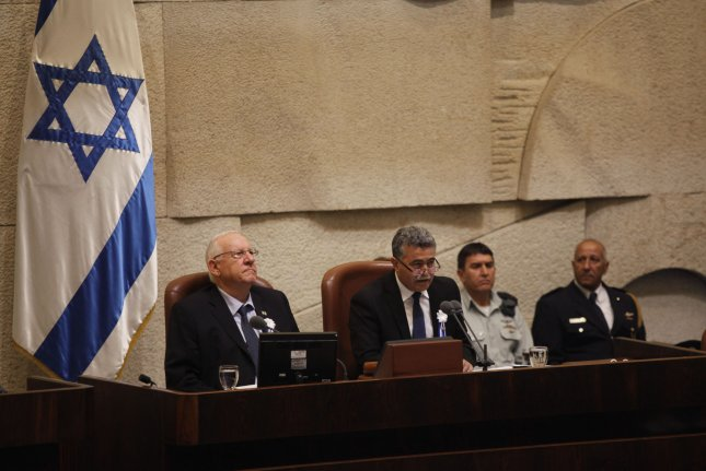 Lawmaker Amir Peretz (C) sits next to Israeli President Reueven Rivlin (L) at the Knesset in Jerusalem, Israel. Israel's High Court ordered Peretz to serve as temporary Knesset speaker until a permanent replacement is determined. File Photo by Heidi Levine/UPI
