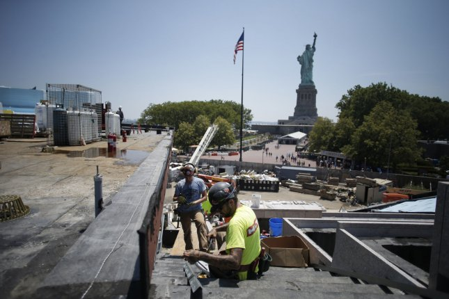 Men wearing hard hats work around the construction site of the upcoming Statue of Liberty Museum on Liberty Island.Photo by John Angelillo/UPI