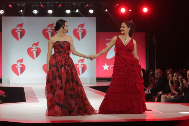 Pro wrestlers, reality TV stars and twins Brie Bella (L) and Nikki Bella walk on the runway at the 15th Annual Red Dress Collection fashion show on February 7 in New York City. Photo by Serena Xu-Ning/UPI