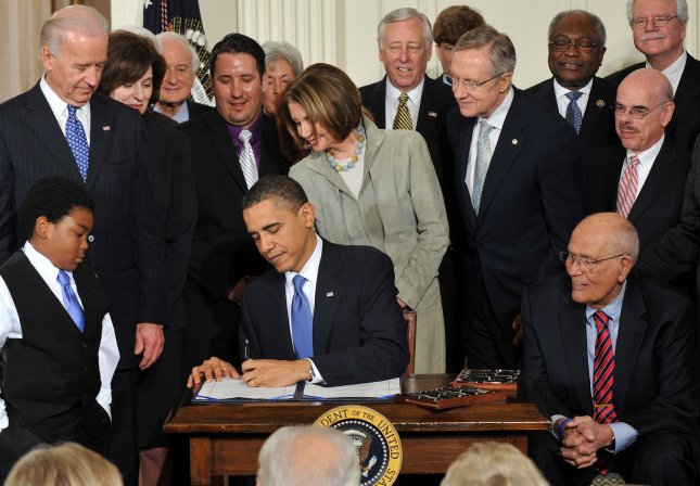 President Barack Obama signs the Health Insurance Reform Bill in the East Room at the White House in Washington, March 23, 2010. Obama was joined by Democratic members of Congress and Marcelas Owens (L) of Seattle. UPI/Kevin Dietsch