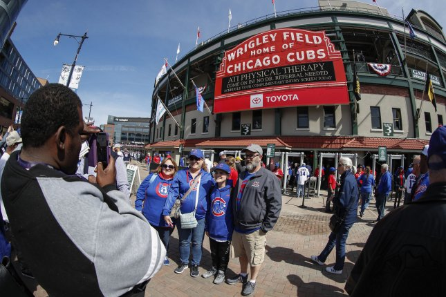 Fans pose for a picture before the Chicago Cubs home opener against Pittsburgh Pirates outside of Wrigley Field on April 8, 2019 in Chicago. One fan has been banned from the ballpark after making a racist gesture. File Photo by Kamil Krzaczynski/UPI