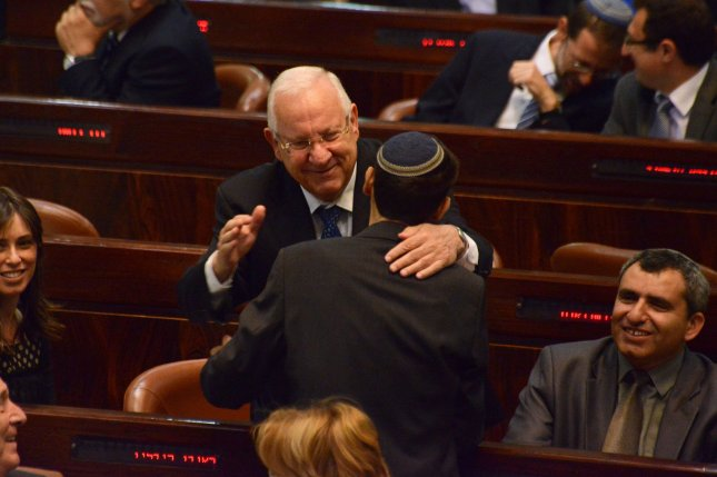 Israeli Knesset member and presidential candidate Reuven Rivlin, center, hugs an unidentified Knesset member during the first round of voting for Israel's 10th president in the Knesset, the Parliament, in Jerusalem, Israel, June 10, 2014. Rivlin from the Likud Party beat Meir Sheetrit from the Hatnua Party in the second round of voting to be elected President of Israel. UPI/Debbie Hill