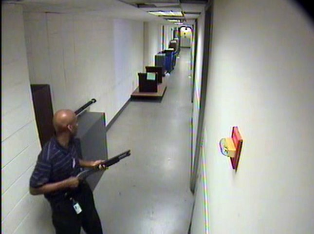 A man armed with a shotgun moves through a hallway in a Washington Navy Yard building Sept. 16, 2013. The gunman, identified as Aaron Alexis, killed 12 people before he was shot and killed by police. This surveillance photo was released by the FBI Sept. 25, 2013. FBI/UPI File