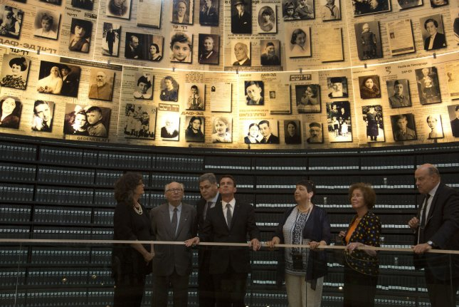 French Prime Minister Manuel Valls (C) visits the Hall of Names Monday during his visit to the Yad Vashem Holocaust Memorial Museum in Jerusalem. Valls is on a three day visit to advance his country's plan to restart Israeli-Palestinian peace efforts, but Israeli Prime Minister Benjamin Netanyahu rejected his suggestion of an international peace summit. Pool photo by Heidi Levine/UPI