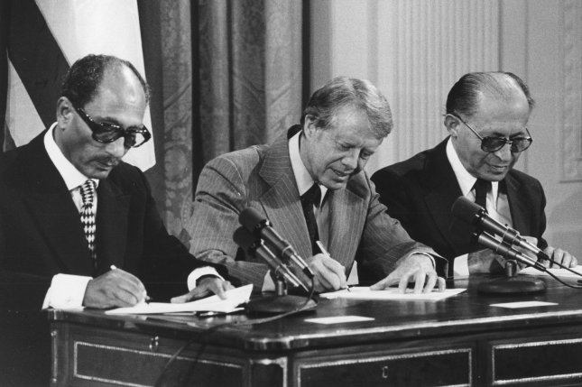 President Anwar Sadat of Egypt (L), President Jimmy Carter (C) and Israeli Prime Minister Menachem Begin sign two agreements providing for negotiation of a full Middle East peace treaty within three months in a ceremony in the east room of the White House on September 17, 1978. File Photo by Darryl Heikes/UPI