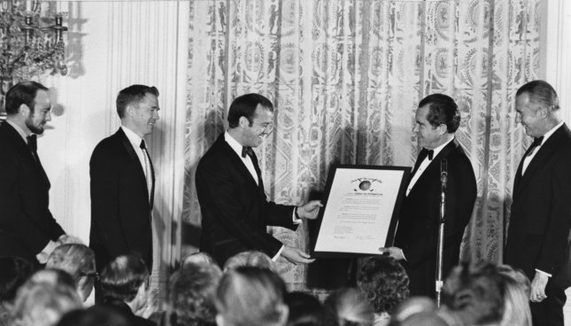 President Richard Nixon (2nd-R) awards the moon-voyaging astronauts of Apollo 14, Edgar Mitchell (L), Stuart Roosa (2nd-L) and Alan Shepard (C) with NASA's Distinguished Service Medal at a White House dinner on March 1, 1971. Shepard and Mitchell walked on the moon February 5, 1971. File Photo by John Full/UPI