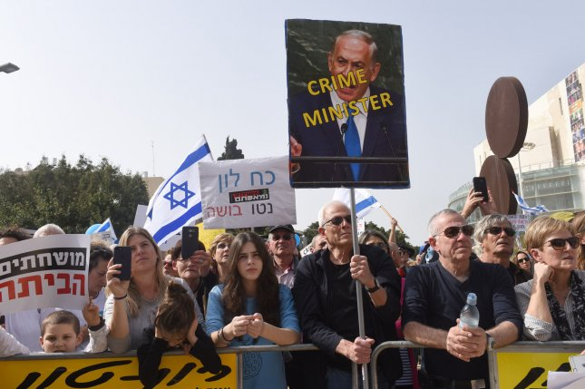 Israeli protesters hold signs during a protest Friday in Tel Aviv, Israel, calling on Prime Minister Benjamin Netanyahu to resign amid a police recommendation that the leader be indicted for bribery, fraud and breach of trust in two corruption cases. Photo by Debbie Hill/UPI