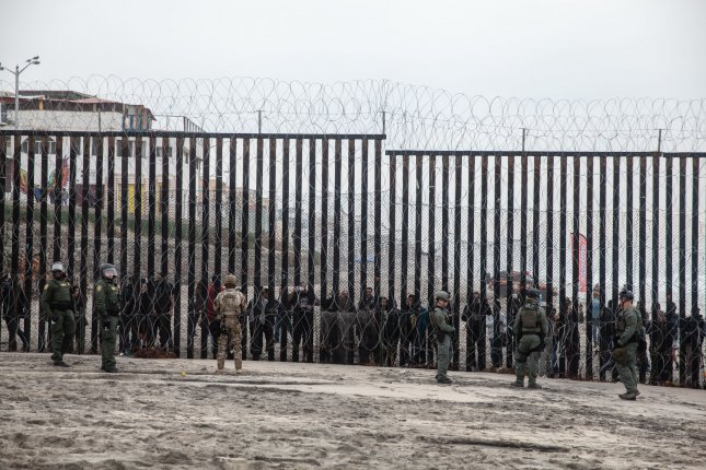 Border Patrol agents stand in front of the border fence that divides the United States and Mexico at Border Field State Park in San Diego on Monday. Photo by Ariana Drehsler/UPI