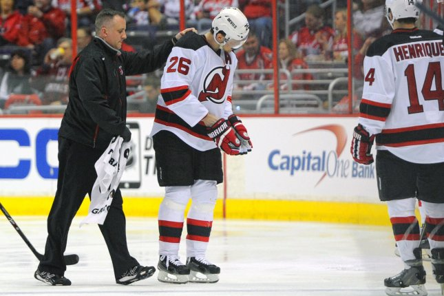 New Jersey Devils left wing Patrik Elias (26) is escorted off the ice after being injured in the first period at the Verizon Center in Washington, D.C. on March 26, 2015. Photo by Mark Goldman/UPI
