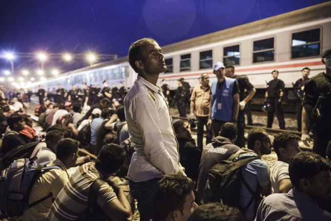 A Pakistani migrant waits Saturday to board a train heading for Austria, in Tovarnik, Croatia. European Union interior ministers on Tuesday approved a plan that would relocate 120,000 migrants through mandatory quotas across the continent. Photo by Achilles Zavalli/UPI
