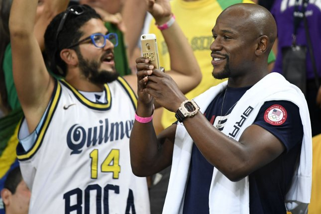 Former World Boxing Champion Floyd Mayweather (R) takes photos during a break in the action between the USA vs Argentina Men's Quarterfinal basketball game at the 2016 Rio Summer Olympics in Rio de Janeiro, Brazil, August 17, 2016. File Photo by Mike Theiler/UPI