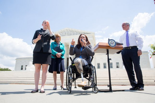 Sen. Tammy Duckworth, D-Ill., (C) joined by Sen. Maggie Hassan, D-N.H. (2nd L) and Sen. Bob Casey, D-Pa., (R) speaks during a news conference in front of the Supreme Court marking the 27th anniversary of the signing of the Americans with Disabilities Act in Washington, D.C. on Wednesday. File Photo by Erin Schaff/UPI