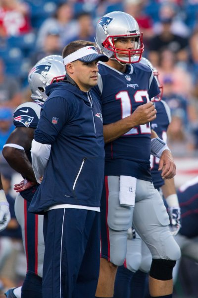 New England Patriots offensive coordinator talks with quarterback Tom Brady prior to a preseason game in 2016. Photo by Matthew Healey/ UPI