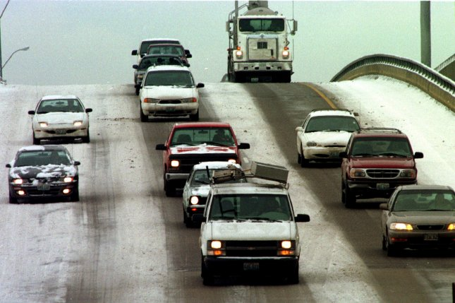 Motorists making their way east down the Vandeventer overpass on Highway 40 go slow as one and a half inches of snow fall on the area January 7, 1999. On January 2, 1974, U.S. President Richard Nixon signed a bill requiring states to limit highway speeds to 55 mph or lose federal highway funds. File Photo by Bill Greenblatt/UPI