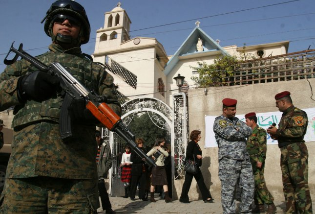 Iraqi policemen stand guard outside Virgin Mary Church, as worshippers leave after Christmas Day Mass in Baghdad, Iraq on December 25, 2008. Christmas Day was declared an official holiday in Iraq for the first time this year. (UPI Photo/Ali Jasim)