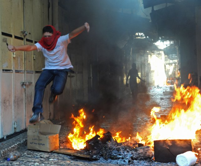 A masked Arab youth jumps over fire after hurling stones at Israeli riot police in Jerusalem's Old City, October 25, 2009. Clashes broke out after Muslim leaders urged Arabs to defend the Al-Aqsa Mosque in Jerusalem against the jewish conquest. UPI/Debbie Hill