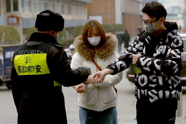 People in Beijing wear mandatory protective face masks and have their temperature checked before they're allowed to enter an international shopping mall. Photo by Stephen Shaver/UPI