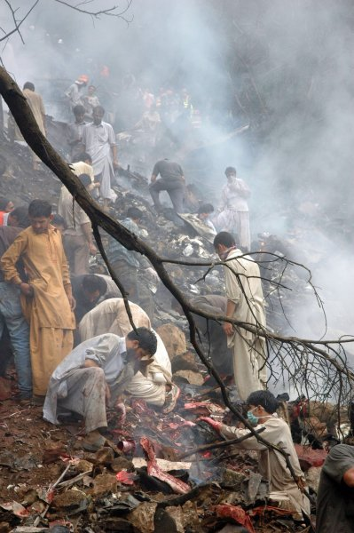 Pakistanis search for survivors after a passenger plane crash in The Margala Hills on the outskirts of Islamabad on July 28, 2010. A Pakistani airliner carrying 150 people crashed in a ball of flames into densely wooded hills above Islamabad during heavy rain and poor visibility, leaving little sign of survivors. UPI/Sajjad Ali Qureshi