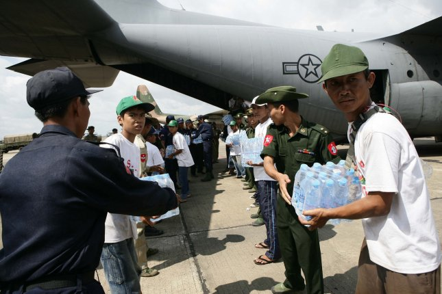 Burmese service members form a line to unload water supplies from a U.S. Air Force C-130 Hercules aircraft at Rangoon International Airport in Myanmar on May 12, 2008. The shipment of water, mosquito nets and blankets arrived on the first of three planned relief flights to provide aid to citizens devastated by Tropical Cyclone Nargis. (UPI Photo/Andres Alcaraz/U.S. Marine Corps)