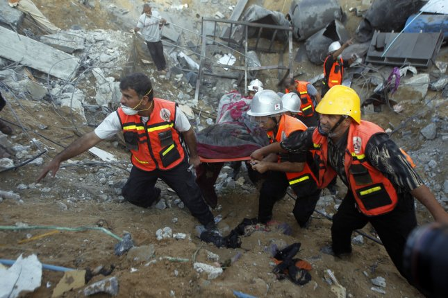 Rescue workers carry the body of a member of al-Najar family, after removing it from under the rubble of their home following an Israeli air strike on Khan Yunis in the southern of Gaza strip , on July 26, 2014. An Israeli air strike in southern Gaza hours before a humanitarian truce was declared killed 20 people, including 11 children, most of them from the Najjar family, medics said. UPI/Ismael Mohamad