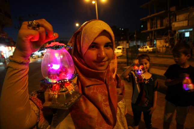 A Palestinian girl holds a traditional lantern in honor of the Muslim holy month of Ramadan, in the Rafah southern Gaza on Wednesday. More than 1.5 billion Muslims around the world will mark the holy month which begins this week. Muslims observe Ramadan by abstaining from food and drink, smoking and sex from dawn until sunset. Photo by Ismael Mohamad/UPI