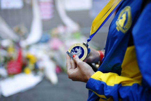 A Boston Marathon runner shows off her medal in front of a makeshift memorial for Boston Marathon bombing victims near the site on Boylston Street in Boston. The trial of accused bomber Dzhokar Tsarnaev started Wednesday. Photo by Matthew Healey/UPI.
